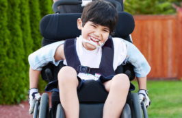 Happy little disabled boy outdoors in wheelchair